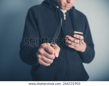 A young man is showing threatening behaviour by waving a knife whilst using a smartphone at the same time