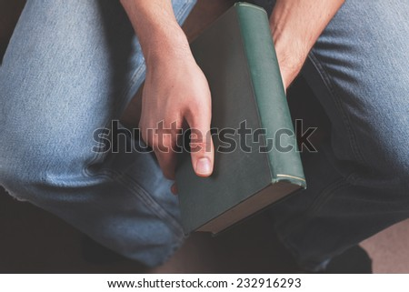 A young man is sitting and holding a big old book
