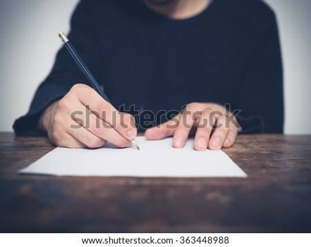 A young man is sitting at a table and is writing with a pencil