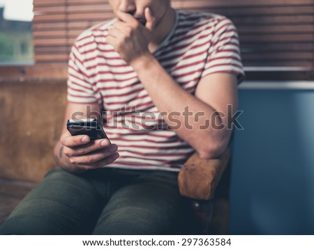 A young man is sitting on a sofa and is using a smart phone at home - stock photo