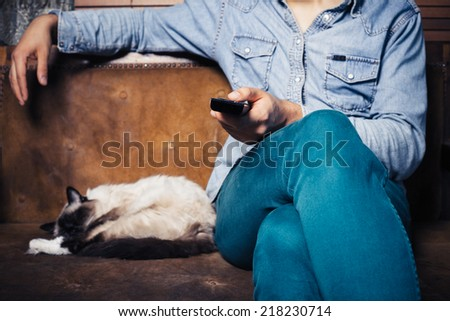A young man is sitting on a sofa with a cat and is watching television - stock photo
