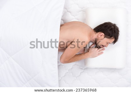 A young man is sleeping on a mattress. Top view. Isolated on white background - stock photo