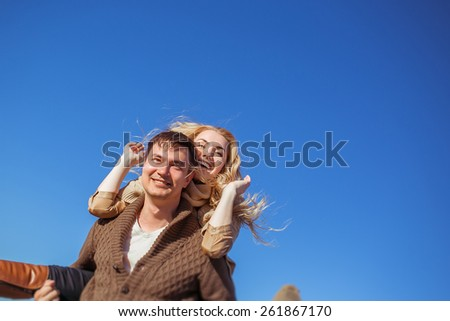 A young man is smiling and holding a laughing young woman on his back. Clothes: casual. - stock photo
