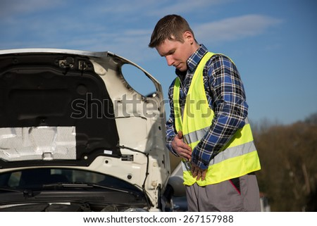 A young man is standing beside his broken car and is fitting his reflective vest. - stock photo