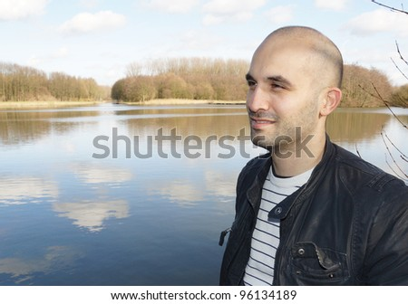 A young man is standing by a lake