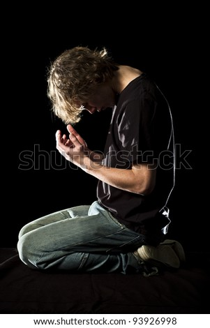A young man kneels and prays in the dark - stock photo