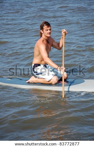 A young man kneels on his stand-up paddle-board - stock photo