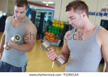 A young man lifting weights at the gym next to a mirror. - stock photo