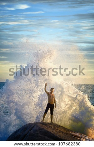 A young man like a god of the sea commands the elements - stock photo