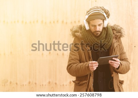 a young man listens to music in an urban image of modern life istagram style toned - stock photo
