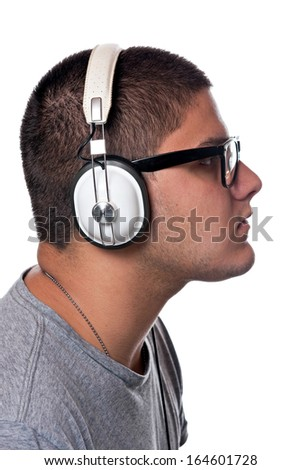 A young man listens to music with a set of head phones over a white background. - stock photo