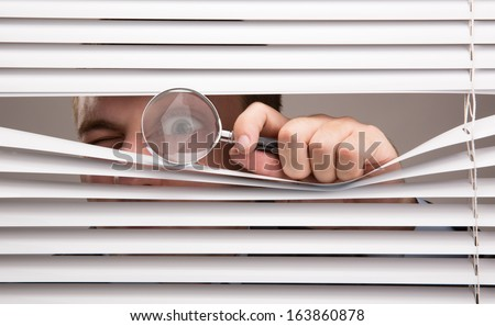 A young man looking through window blinds