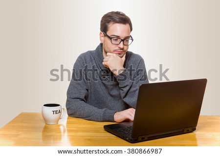 A young man looks frustrated on his laptop screen
