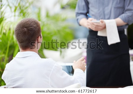 A young man makes a restaurant reservation