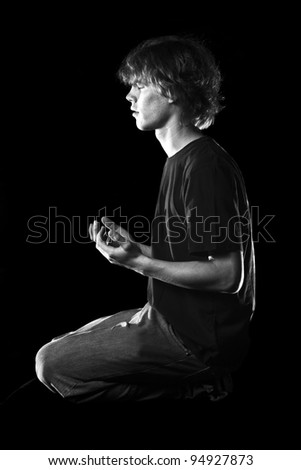 A young man meditates in prayer - stock photo
