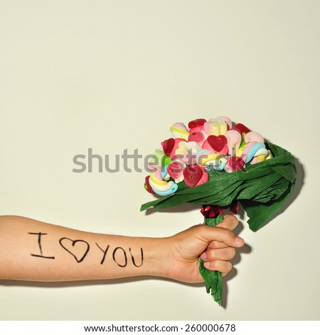 a young man offering a candy bouquet and the sentence I love you written in his forearm - stock photo