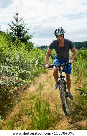A young man on a mountain bike in grassy landscape