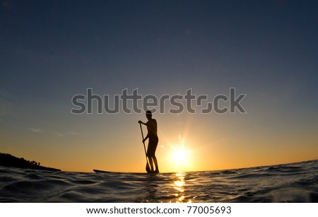 A young man paddles his surfboard in to shore at sunset