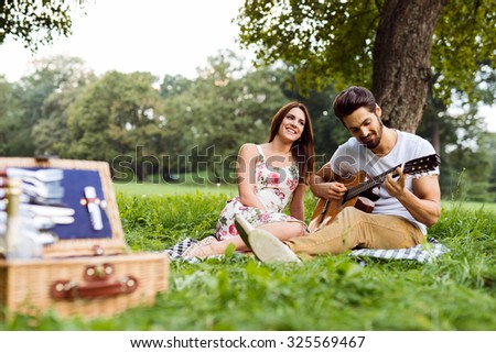A young man playing a song on his guitar for his beautiful girlfriend. Selective focus.