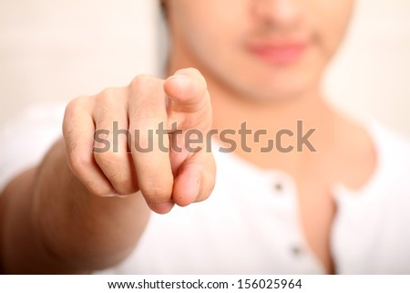 A young man pointing at you. Focus on Finger.