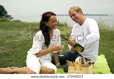 A young man pours a glass of wine for his beautiful partner during a romantic picnic - stock photo