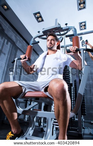 A young man practicing bodybuilding and weight lifting in the Gym. - stock photo