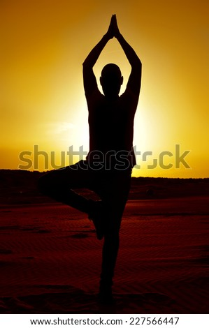 a young man practicing the yoga tree pose in backlight at sunset