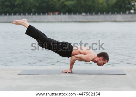 a young man practicing yoga asanas in the city on the waterfront