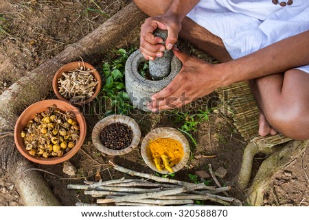 A young man preparing ayurvedic medicine in the traditional manner.  - stock photo