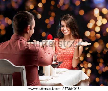 A young man presenting engagement ring to his girlfriend - stock photo