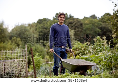 A young man pushing a wheelbarrow on an allotment - stock photo