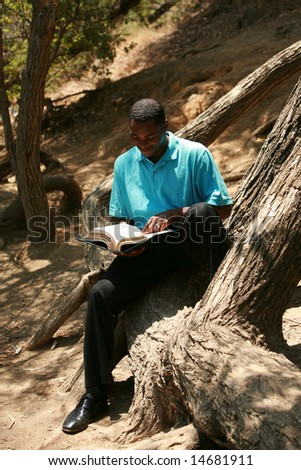 a young man reads a book outside