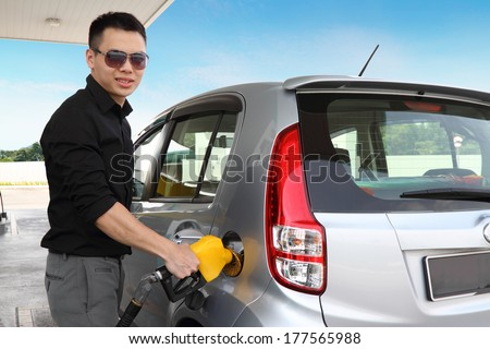 A young man refueling his car - stock photo