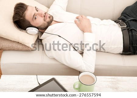 A young man relaxing and listening to music on the couch.  - stock photo