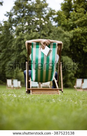 A young man relaxing on a deckchair in St James Park, holding a guidebook