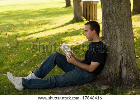 A young man relaxing under a tree, reading a book - stock photo