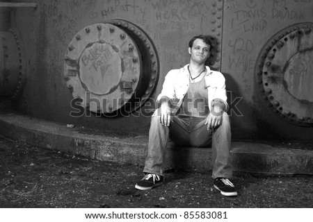 A young man resting against an iron wall