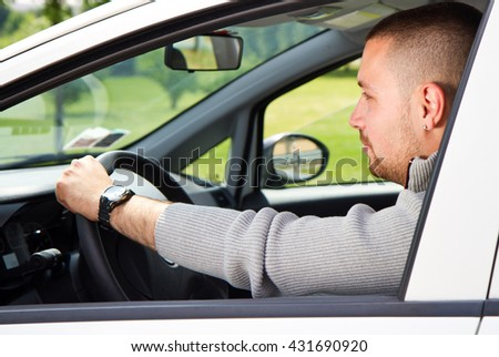 A young man rides in a car