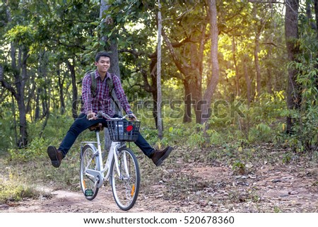 A young man riding a bike in the forest on the mountain.on sunset