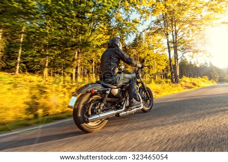 A young man riding a chopper on a road in morning sun - stock photo