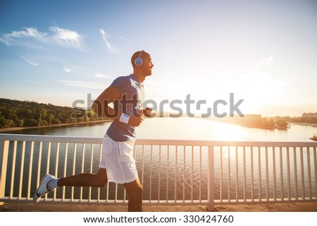 A young man running on the bridge along a river. Lens flare, warm tones. - stock photo