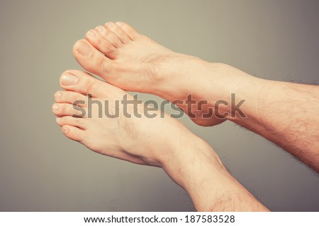 A young man's feet against a plain background