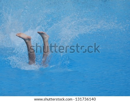 A young man's legs disappearing as he dives into the swimming pool.. - stock photo