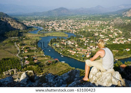 A young man, sat looking out over a view in Turkey