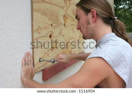 A young man screwing plywood over a window on his home in preparation for a hurricane.