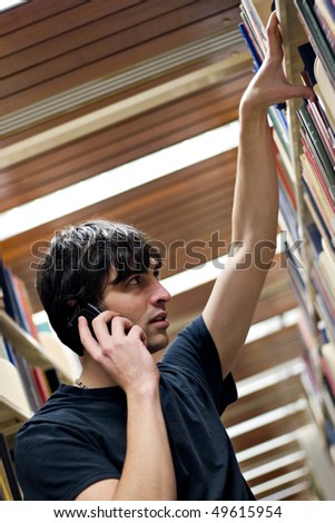 A young man searching for a book or topic at the library while doing research of some sort. - stock photo