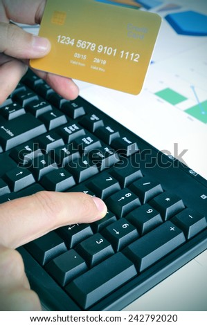 a young man shopping online with a simulated credit card - stock photo