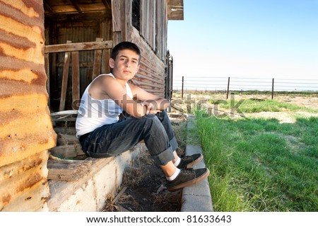 A young man sits in the doorway of an old abandoned barn in a rural area. - stock photo