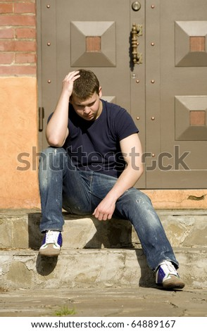 A young man sits on the stairs near the house - stock photo