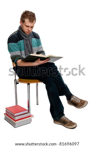 A young man sits reading a book in the studio posing on a white background - stock photo